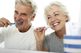 Senior couple brushing teeth to care for dental implants