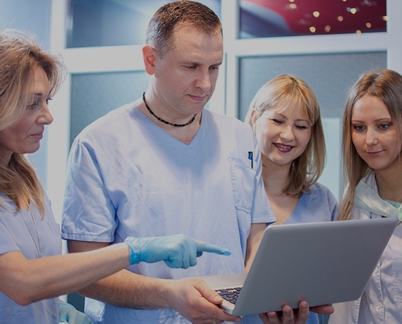 Dental team looking at laptop computer