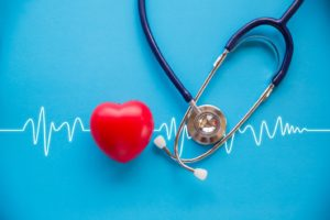 small red heart and stethoscope on blue background