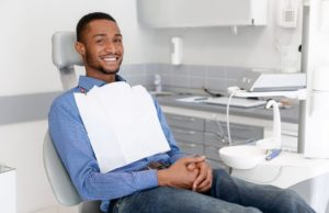 Smiling man at appointment to maximize dental insurance benefits